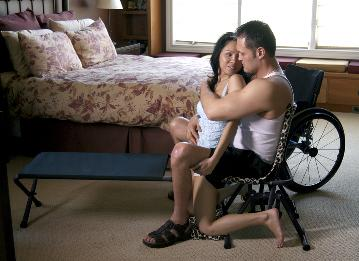 A disabled man sitting on the IntimateRider chair while hugging an able-bodied woman, his wheelchair in the background.